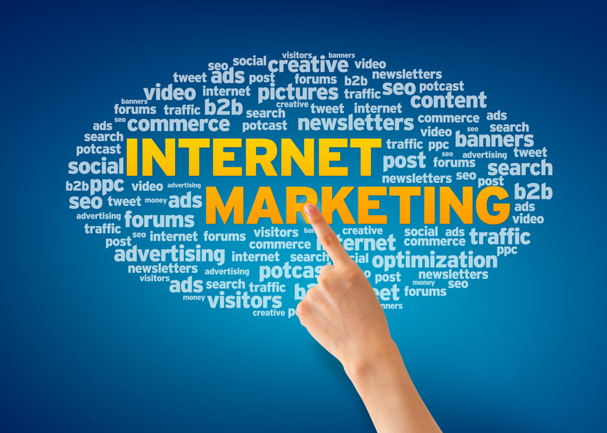 Hand pointing at an Internet Marketing word cloud on blue background.